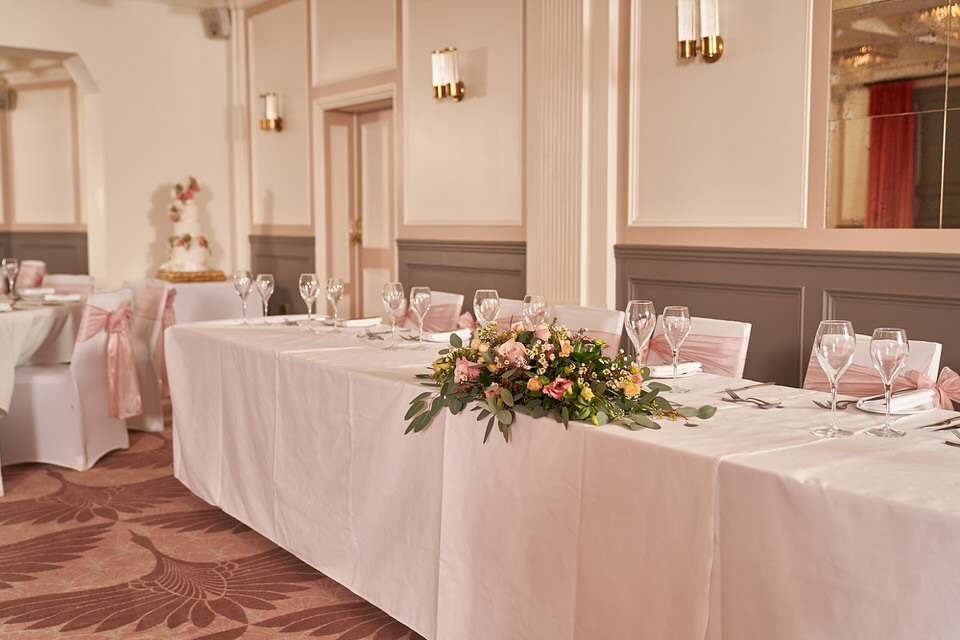 The top table in The Coach Room at the Bedford Swan Hotel laid out for wedding breakfast.