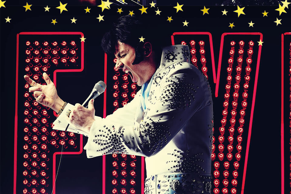 Michael Clews dressed as Elvis performing in front of a neon Elvis sign
